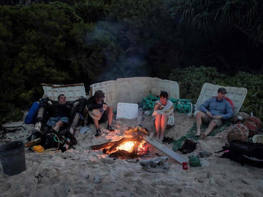 I membri del team di pulizia della spiaggia seduti attorno al fuoco dopo aver raccolto la spazzatura da una spiaggia sull'isola di Henderson. (Photo by Iain McGregor / STUFF / AFP)