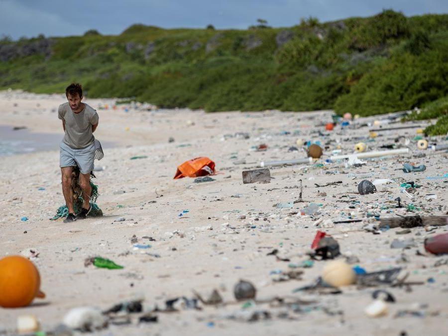 TUn membro del team di pulizia della spiaggia mentre raccoglie spazzatura da una spiaggia sull'isola di Henderson. (Photo by Iain McGregor / STUFF / AFP)