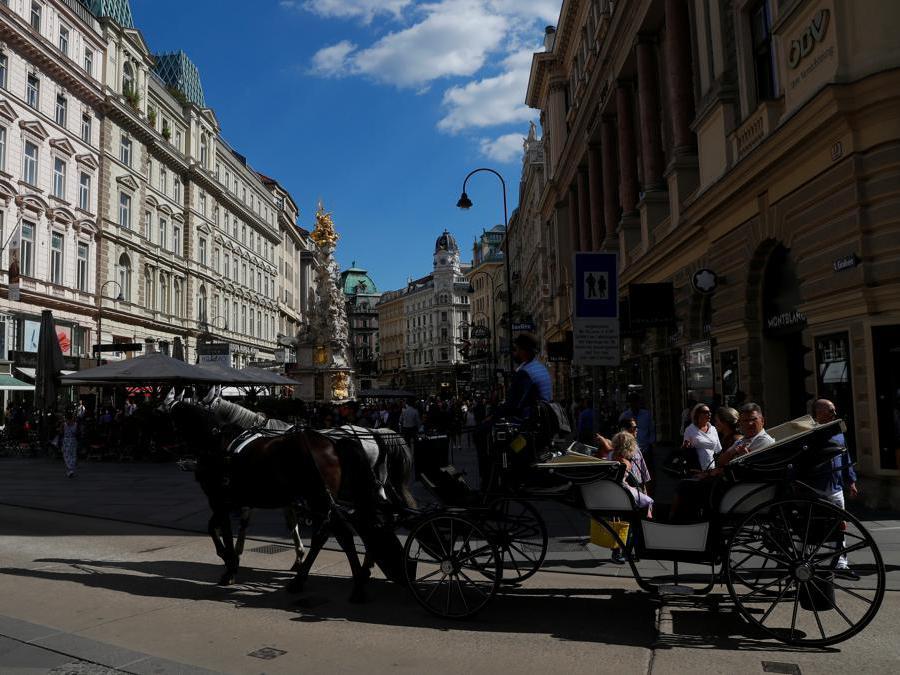 I turisti fanno un giro in una tradizionale carrozza trainata da cavalli Fiaker vicino a Graben, nel centro di Vienna. REUTERS/Leonhard Foeger