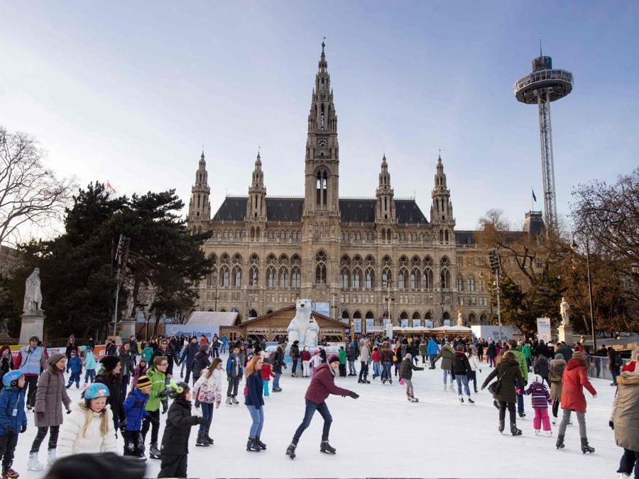Le persone pattinano sul ghiaccio di fronte al Municipio di Vienna, progettato nel 1883 dall'architetto austriaco Friedrich von Schmidt (1825-1891) a Vienna. (Photo by Joe KLAMAR / AFP)
