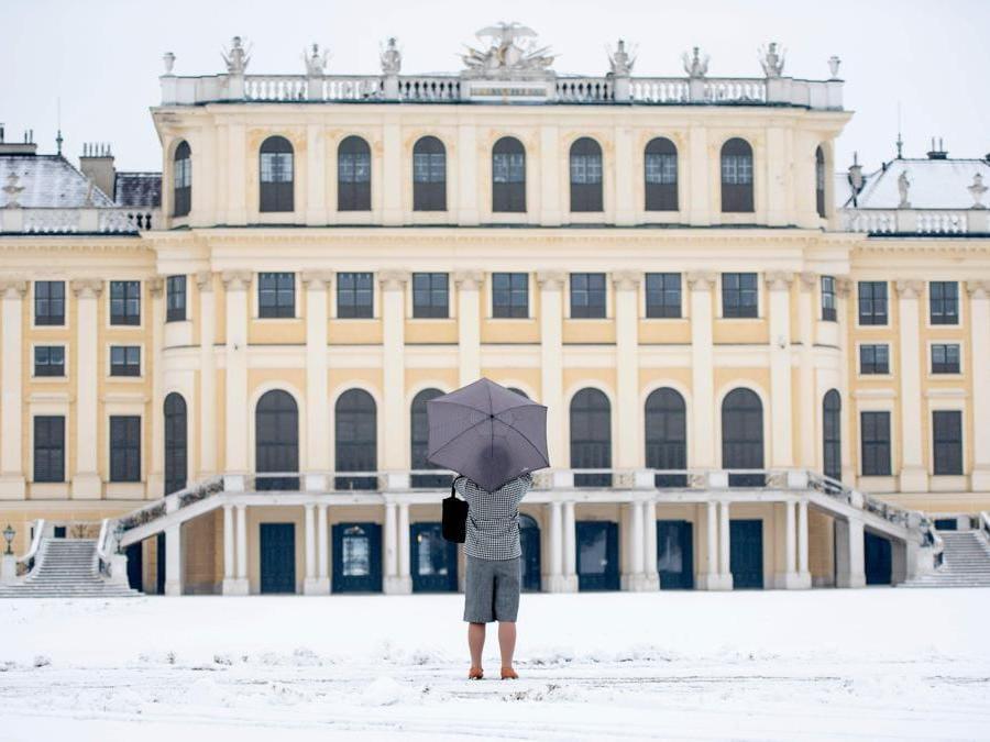 Un turista si trova sul giardino coperto di neve per scattare foto al castello di Schönbrunn a Vienna. (Photo by JOE KLAMAR / AFP)